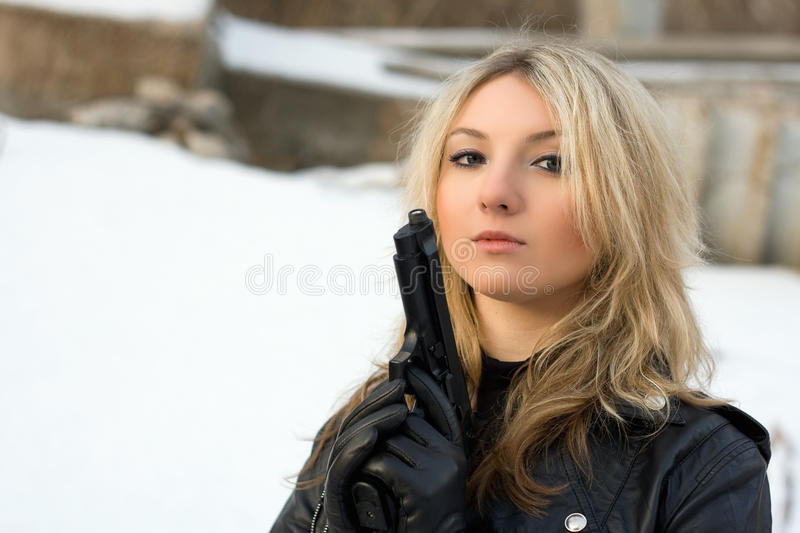 Hot girl against the snow. Hot girl holding a gun against the snow royalty free stock image