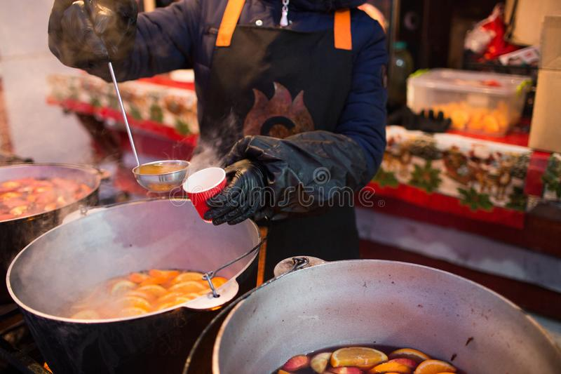 Hot gluhwein or mulled wine in a cauldron at fair, local treat, warm and spicy. A hot wholesome traditional citrus drink on fair. stock photos