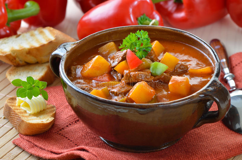 Hot goulash soup. Typical Hungarian goulash soup with baguette stock photo