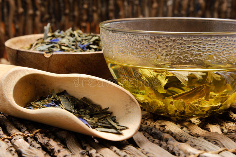 Hot green tea. In a glass cup with a tea leafs on wooden shovel. Shallow Depth of Field (Focus on tea stock photos