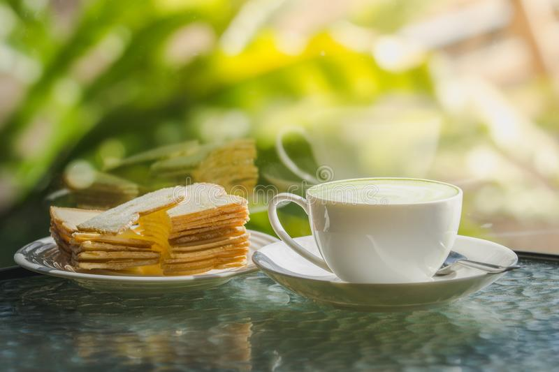 Hot green tea with biscuits on the table and a reflection mirror royalty free stock image