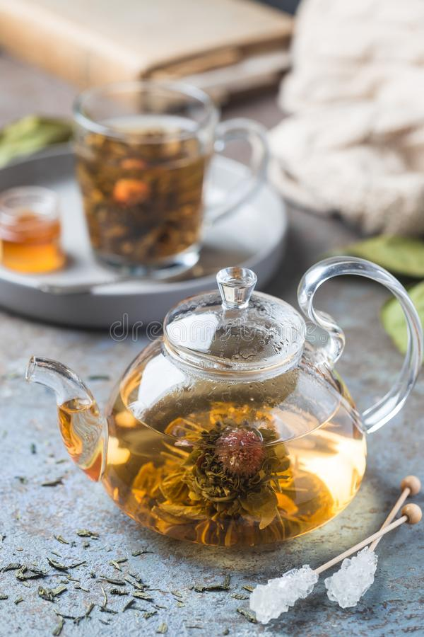 Blooming tea flower. Hot green tea drink. Teapot and glass cup with blooming tea flower inside against stone background stock photography