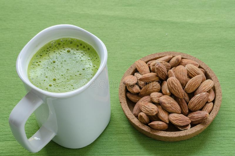 Hot green tea latte in lazy time with almonds nut. royalty free stock photography