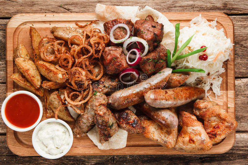 Hot grilled meat, fried sausages and baked potato royalty free stock photo