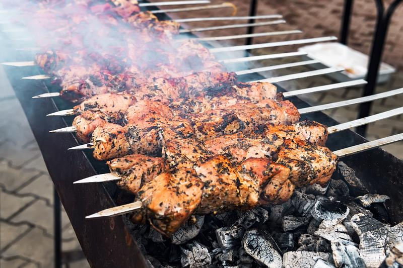 Hot grilled pork kebab or barbecue kebab on charcoal background with herbs and spices closeup. Photo barbecued pork royalty free stock photos