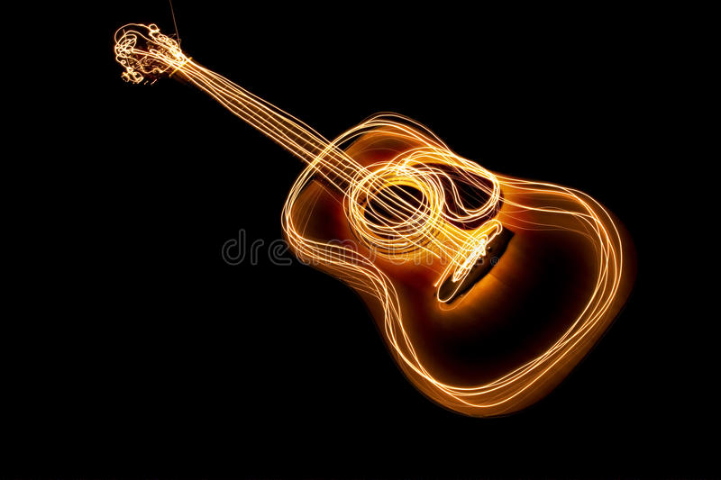 Hot guitar. Guitar with burning stripes on a black background stock photography
