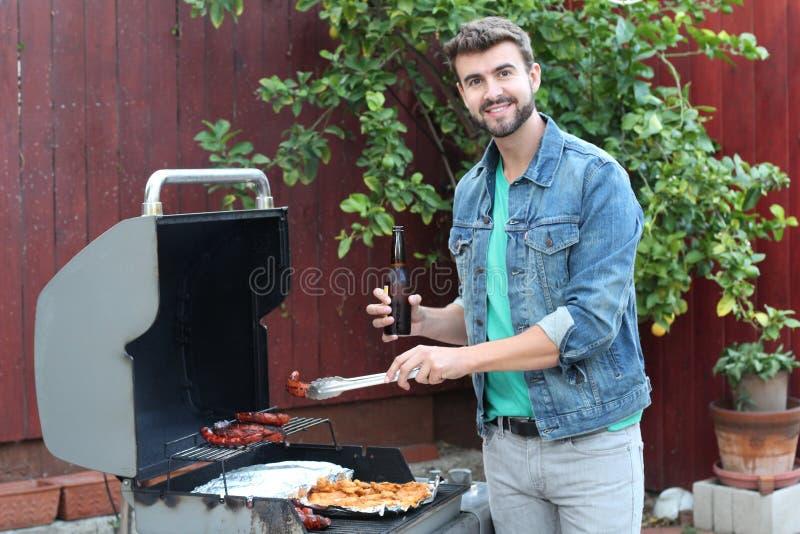 Hot guy preparing dinner in barbecue.  stock photo