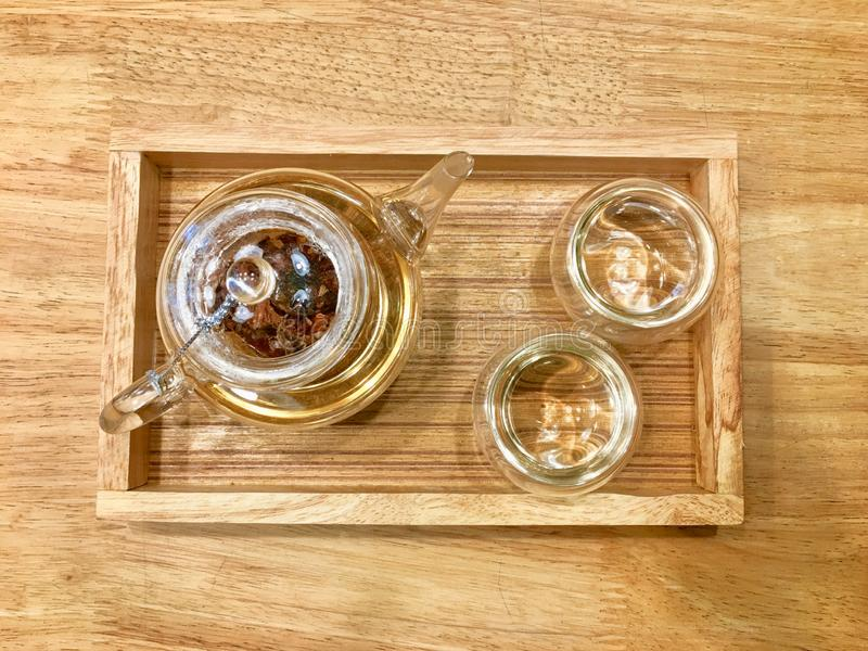 Hot herbal tea inside transparent cup and glass jar on the light brown wooden tray put on wooden table. royalty free stock photo