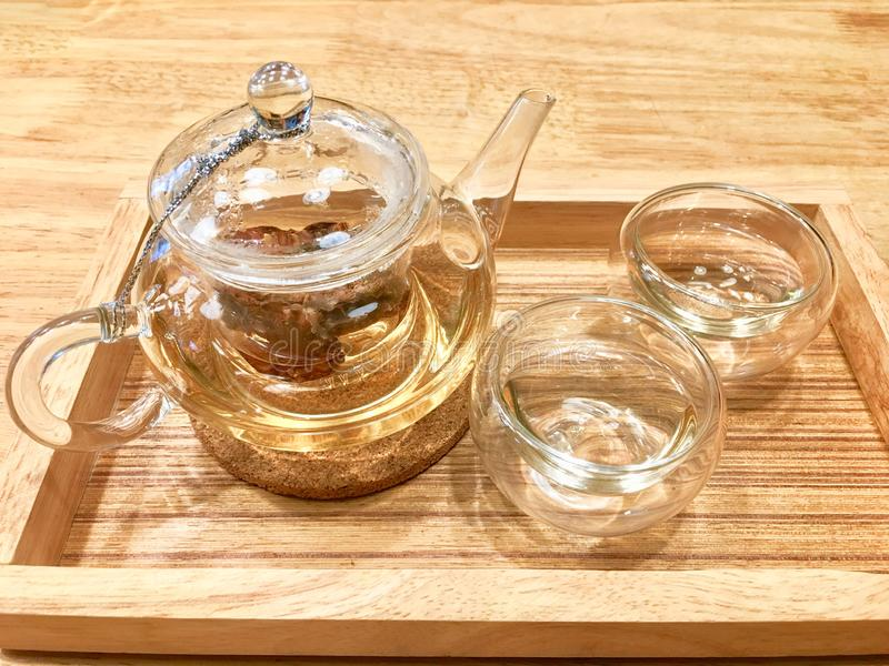 Hot herbal tea inside transparent cup and glass jar on the light brown wooden tray put on wooden table. stock photography