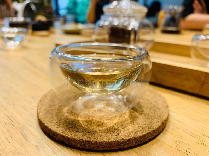 Hot herbal tea inside transparent double wall glass on the light brown wooden tray put on wooden table. stock image