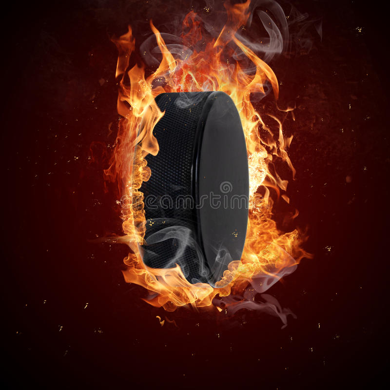 Hot hockey puck. In fires flame stock photo