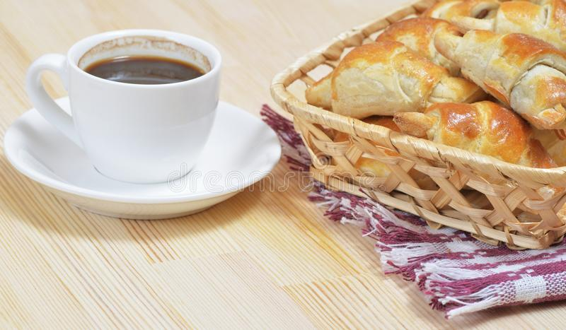Hot homemade croissants in wicker basket on a wooden table royalty free stock images