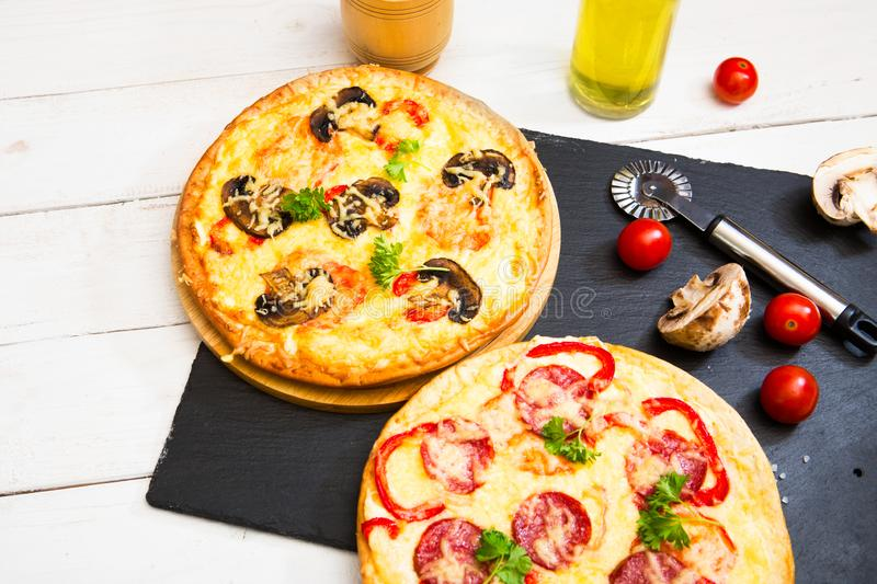 Hot homemade pepperoni pizza on white wooden table and black stone surface. Ready to eat. Hot homemade pepperoni pizza on white wooden table and a black stone stock photo