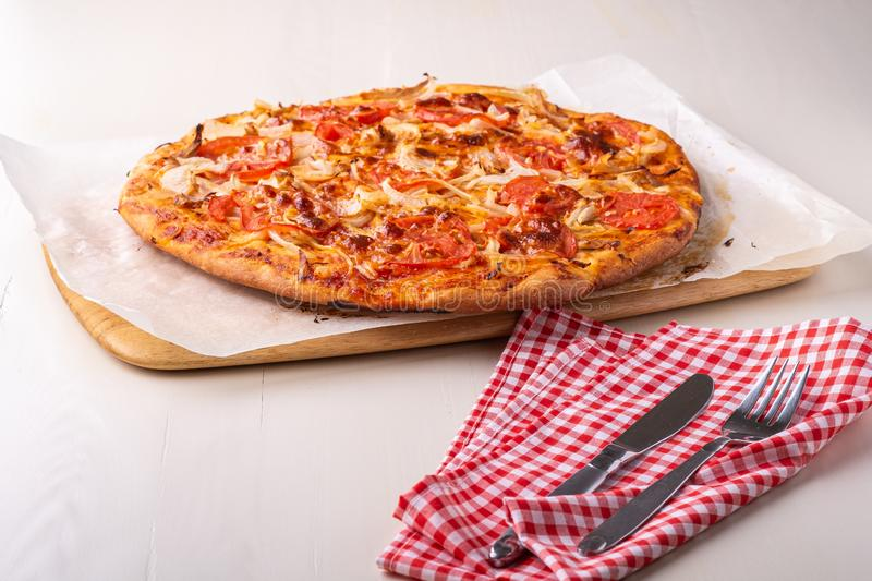 Hot homemade pizza with chicken meat, tomatoes, onions near with cutlery fork and knife on red tablecloth, angle view royalty free stock photography
