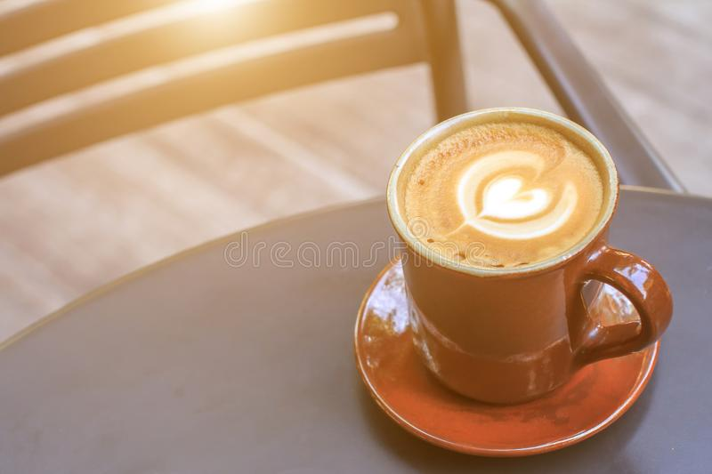 Hot latte coffee cup on black metal table in coffee shop. royalty free stock photos