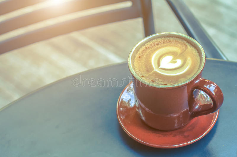 Hot latte coffee cup on black metal table in coffee shop. stock image
