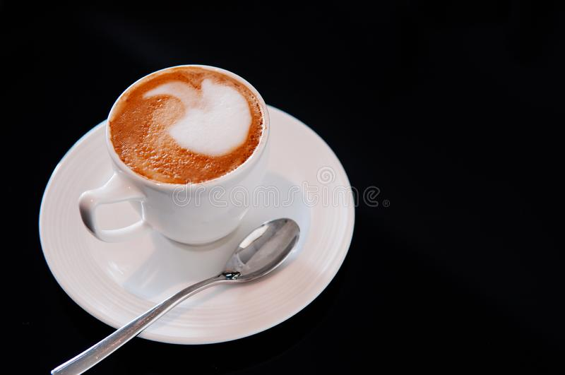 Hot latte coffee cup with spoon isolated on black background royalty free stock image