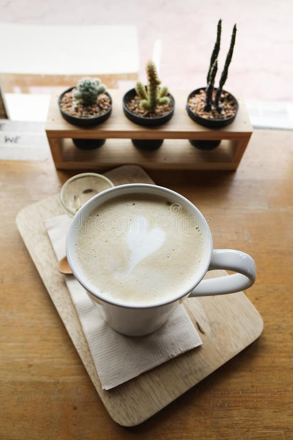 Hot latte coffee on wooden plate stock photo
