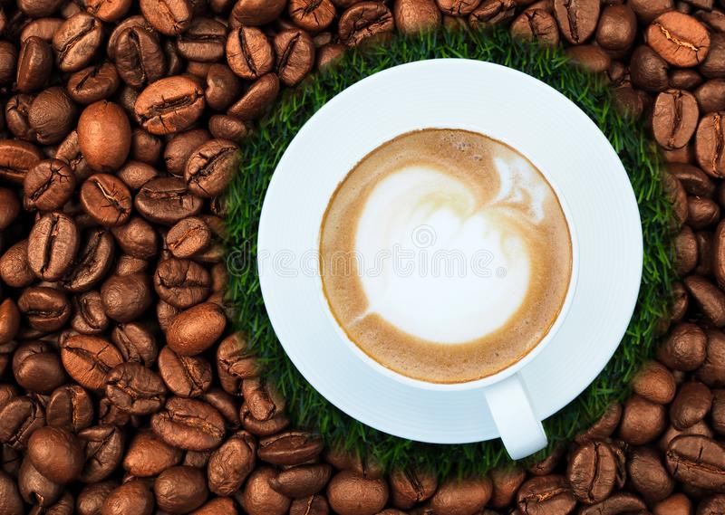 Hot latte coffee in white cup on coffee beans background royalty free stock images