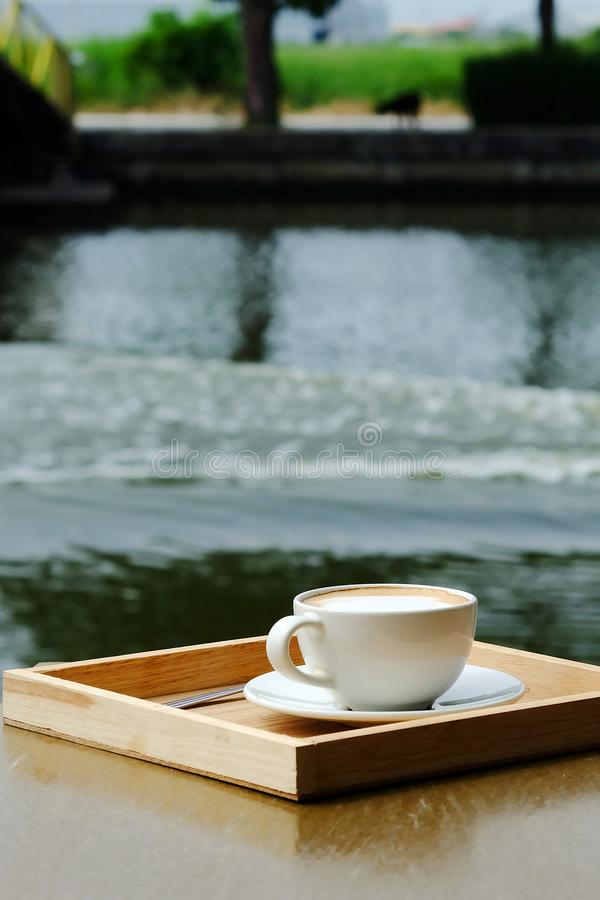Hot latte coffee in white cup on table beside river and space for write wording, served in a shop beside the river in a relax time. With space for write wording royalty free stock images