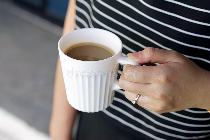 Hot Latte - Holding a cup of coffee with milk on blurred background. royalty free stock photography