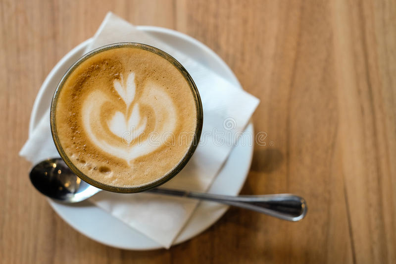 Hot latte with latte art of tulip flower on wooden table stock photography