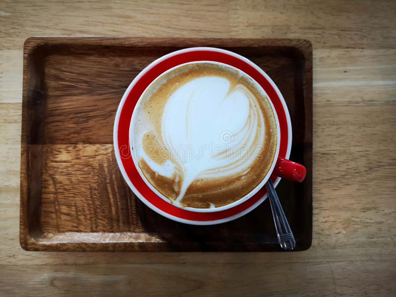Hot latte in a red cup served on a wooden tray on a wooden table. Dav_vivid, art, heart, breakfast, morning, drink, warm, object, nobody royalty free stock photos