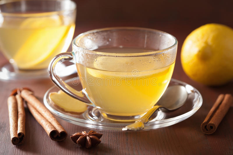 Hot lemon ginger cinnamon tea in glass cup stock images