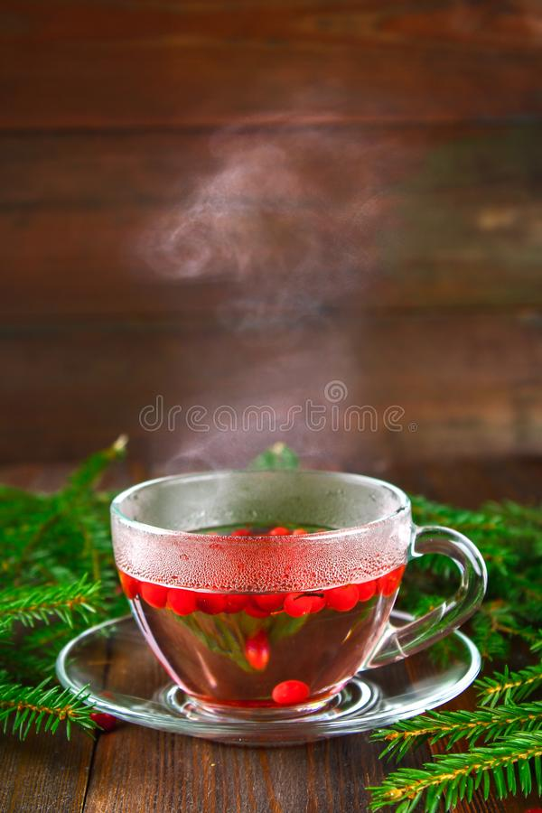 Hot lingonberry, cranberry, foxberry, cowberry tea in glass cup, rustic background. Hot lingonberry, cranberry, foxberry, cowberry tea in glass cup, rustic stock photos