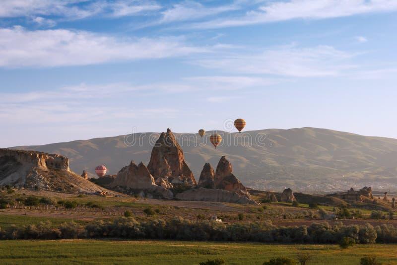 Hot luftar ballongen som flyger över Cappadocia arkivbild