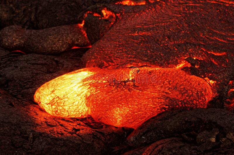 Hot magma emerges from a crack in the earth stock photo