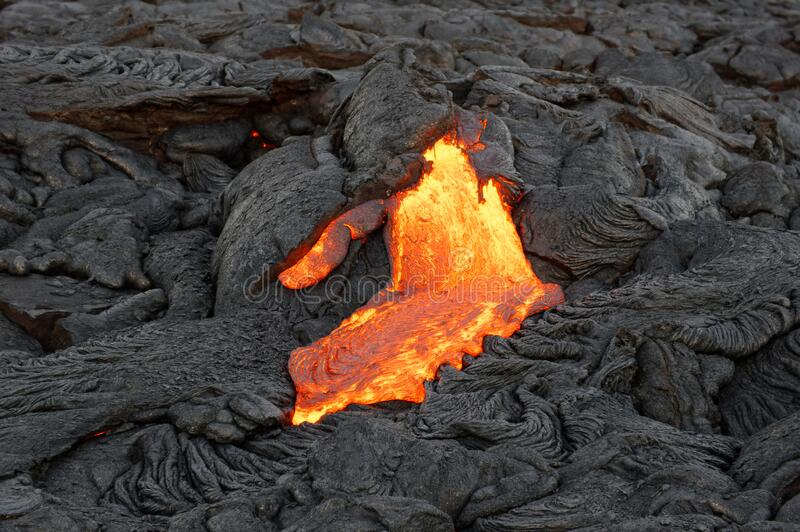 Lava flowing out of a fissure stock image