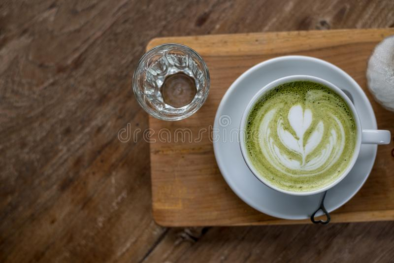 Hot Matcha Green Tea Latte in White Cup on Wood plate with some Water in Glass on Wooden table royalty free stock images
