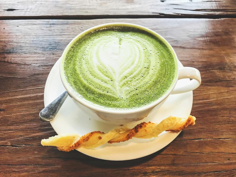 Hot matcha green tea milk latte with creamy milk is heart-shaped pattern, a little sugar, bread and teaspoon in a cup on the stock images