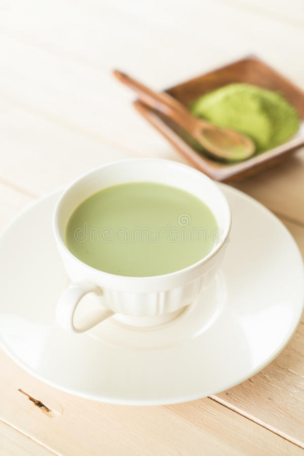 Hot matcha latte. On wood stock photography