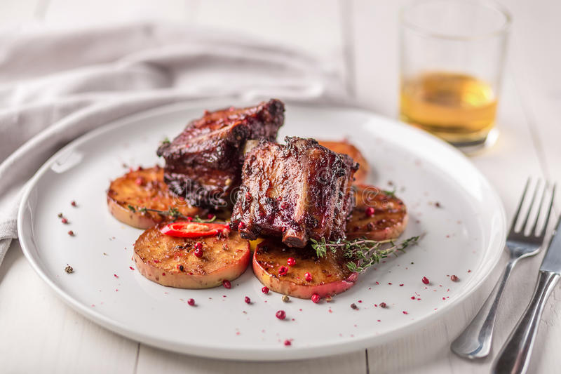 Hot Meat Dishes. Pork ribs grilled with peppers and apples. On a white plate. Wooden background royalty free stock images