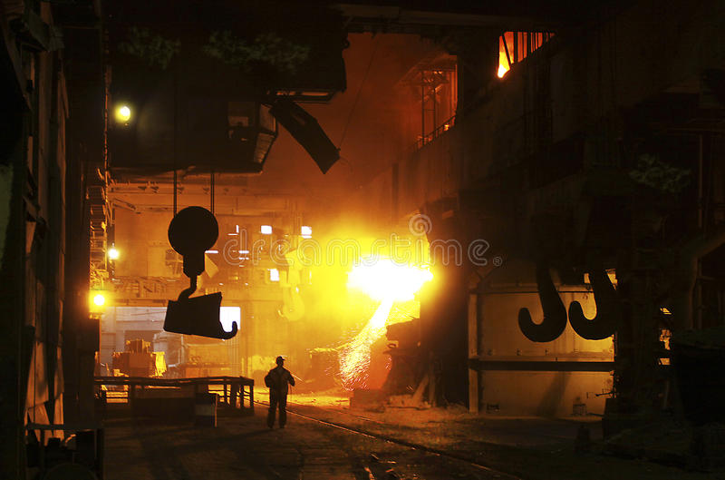 Hot metal melted in the factory. Worker walking along on steel shop stock images