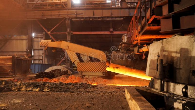 Hot metal production at the factory, metallurgy concept. Stock footage. Molten steel flowing in metallurgical chute stock photos