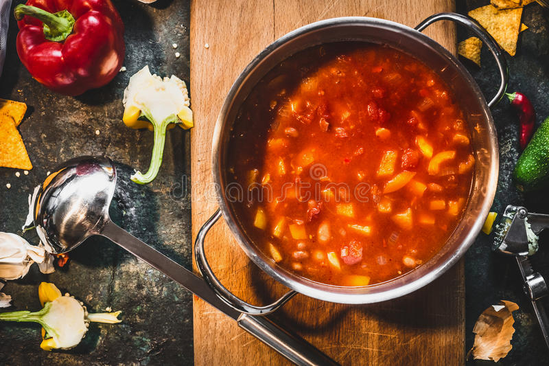 Hot Mexican spicy soup in cooking pot with ladle on rustic kitchen table background. Top view stock image