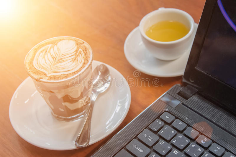 Hot milk latte art coffee on wooden table .Mock up Blank screen. Of Laptop with a cup of coffee on white table in office .Tea cup and pot stand on wooden table stock photo