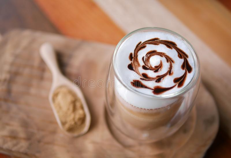 Hot mocha coffee latte art chocolate heart shape spiral glass on table background, vintage style royalty free stock photography