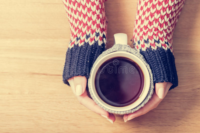 Hot mug of tea warming woman`s hands in retro jumper. Hot mug of tea warming woman`s hands in retro woollen jumper. Wooden table royalty free stock photography
