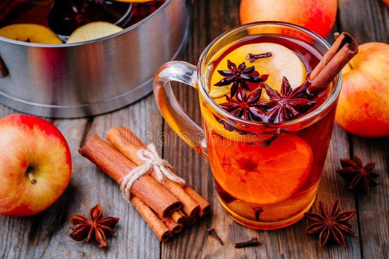 Hot mulled apple cider with cinnamon sticks, cloves and anise royalty free stock photography