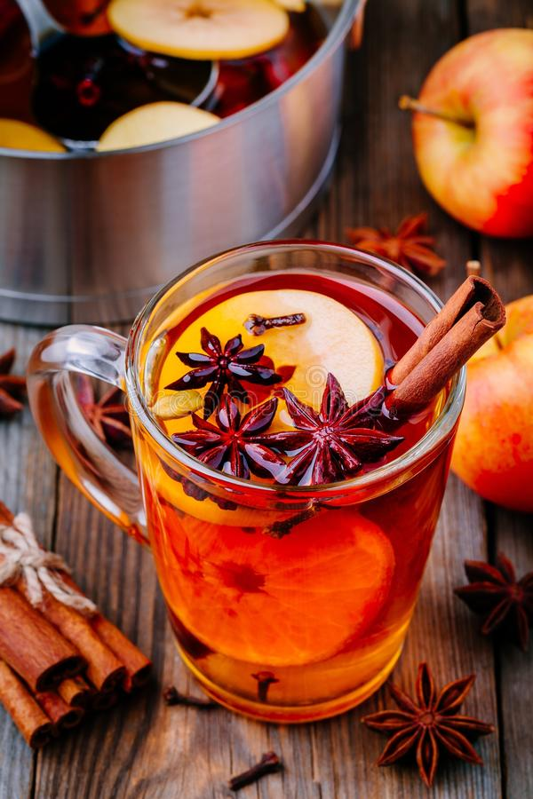 Hot mulled apple cider with cinnamon sticks, cloves and anise. On wooden background stock photos