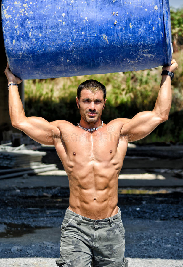 Hot, muscular construction worker shirtless carrying barrel stock images