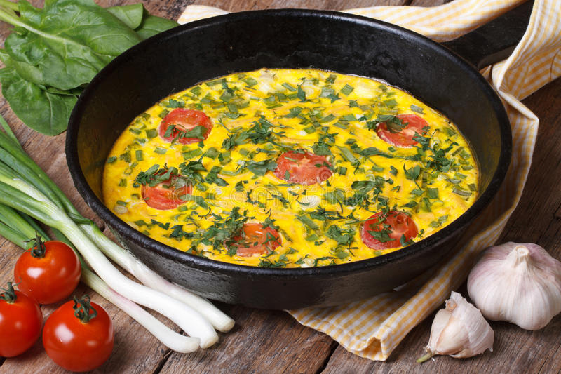 Hot omelette with herbs, tomatoes in a pan and vegetables. Hot omelette with herbs, tomatoes in a pan, and vegetables on the table closeup stock images