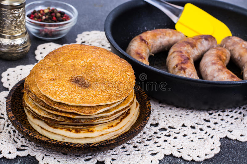 Hot pancakes with homemade sausage in frying pan. Studio Photo stock images