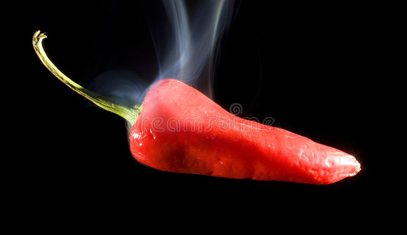 Hot pepper. Red pepper on black so hot that smoke is rising royalty free stock photo