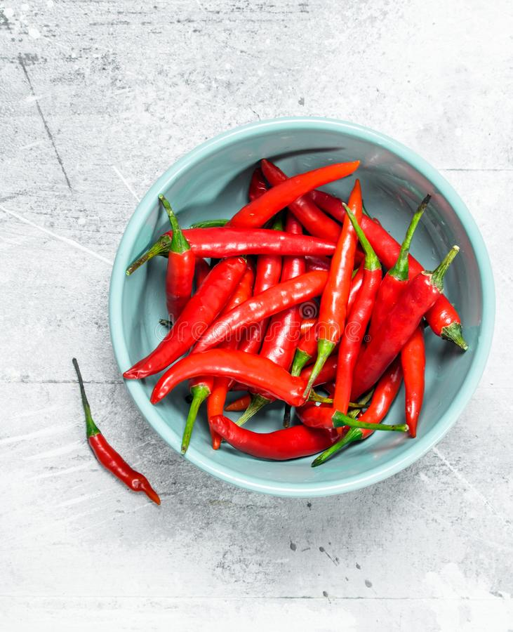 Hot pepper in bowl. On white rustic background royalty free stock photography