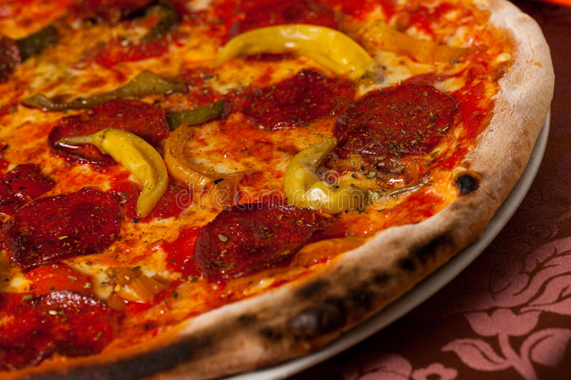 Hot pizza with chili and salami served on a plate in italian royalty free stock photography